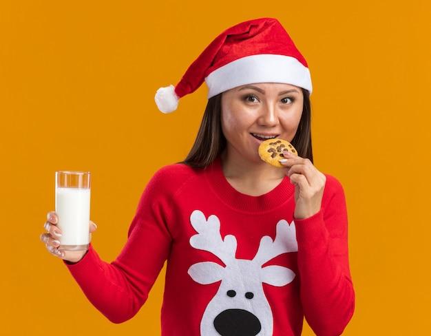 Sorridente giovane ragazza asiatica che indossa il cappello di natale con il maglione che tiene un bicchiere di latte cercando i biscotti isolati sulla parete arancione