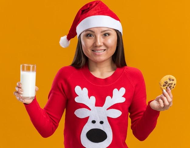 Sorridente giovane ragazza asiatica che indossa il cappello di natale con il maglione che tiene un bicchiere di latte con i biscotti isolato sulla parete arancione