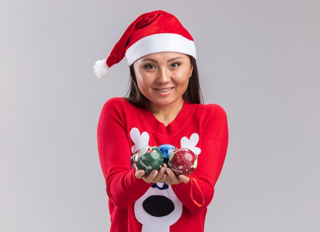 Smiling young asian girl wearing christmas hat with sweater holding out christmas tree balls at camera isolated on white background