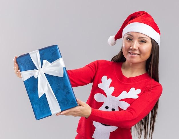 Улыбающаяся молодая азиатская девушка в новогодней шапке со свитером, протягивая подарочную коробку перед камерой, изолированной на белом фоне