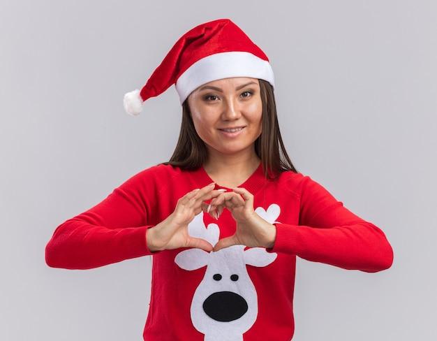 白い背景で隔離の心のジェスチャーを示すセーターとクリスマス帽子をかぶって笑顔の若いアジアの女の子