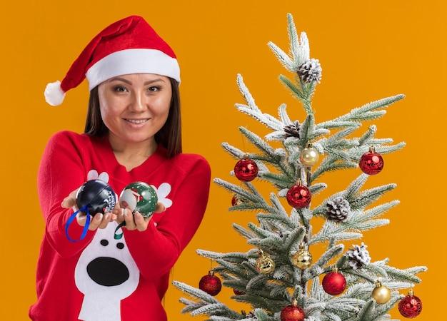 Улыбающаяся молодая азиатская девушка в новогодней шапке со свитером стоит рядом с елкой, протягивая елочные шары на камеру, изолированную на оранжевом фоне