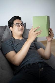 Усмехаясь книга чтения молодого азиатского человека на софе.