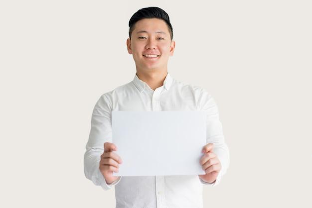 Улыбаясь молодой азиатский человек, показывая бумагу на камеру