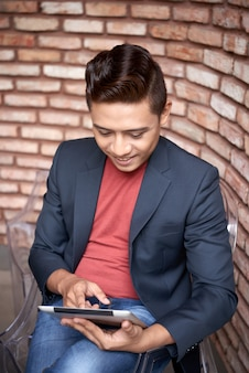 Smiling young asian man sitting next to brick wall and using tablet