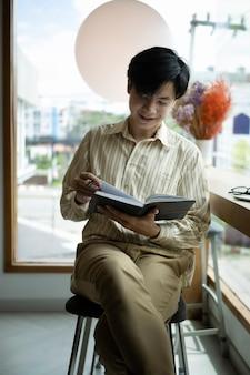 Улыбающийся молодой азиатский человек сидит в ярком офисе и читает книгу.
