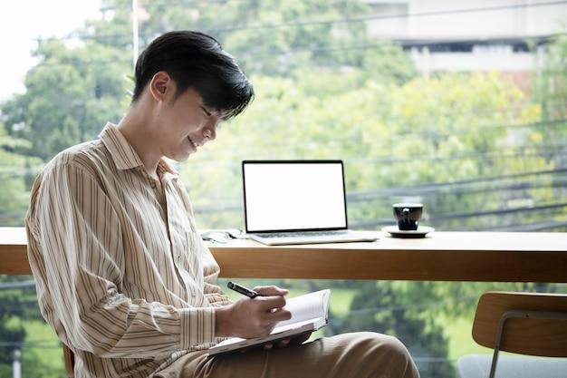 Улыбающийся молодой азиатский человек сидит в ярком офисе и писать новую идею на ноутбуке.