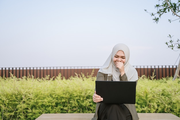 Smiling young asian muslim woman in green suit and working on a computer at park.