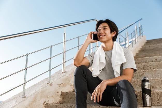 해변에서 계단에 앉아 젊은 아시아 운동가 웃고, 휴대 전화로 이야기