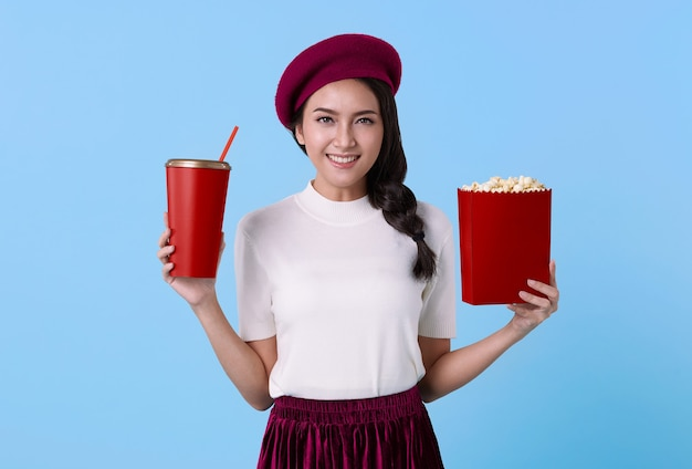 Smiling young asian teen girl watching movie film holdding bucket of popcorn cup of soda isolated on blue background. people lifestyle concept.