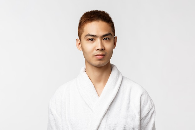 Smiling young asian in white bathrobe