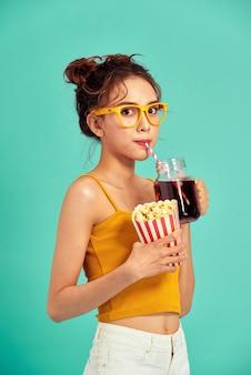 Улыбается молодая азиатская женщина ест попкорн и пить соду, изолированных на синем.