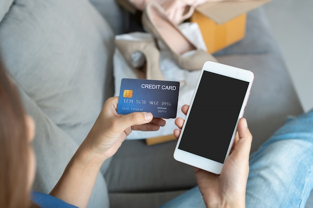 Smiling young asian woman holding credit card while using mobile phone and sitting on sofa at home, digital lifestyle with technology, e-commerce, shopping online concept, copy space for text message.