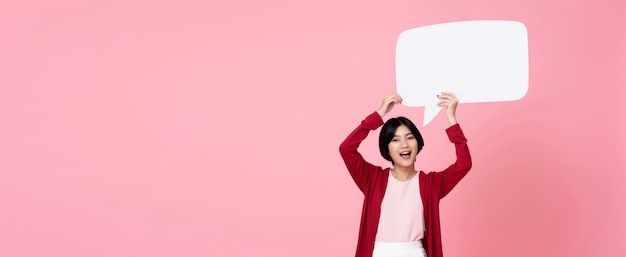 Smiling young asian woman holding empty speech bubble in pink background