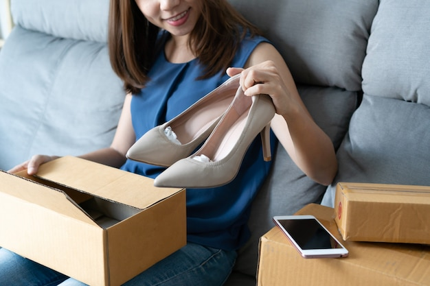 Smiling young asian woman looking at her new high heel shoe and sitting on sofa at home, digital lifestyle with technology, e-commerce, shopping online concept