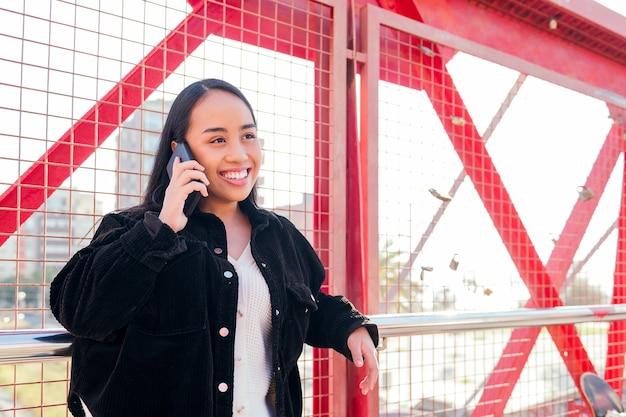 빨간 울타리에 기대어 전화로 야외에서 말하는 웃고 있는 젊은 아시아 여성