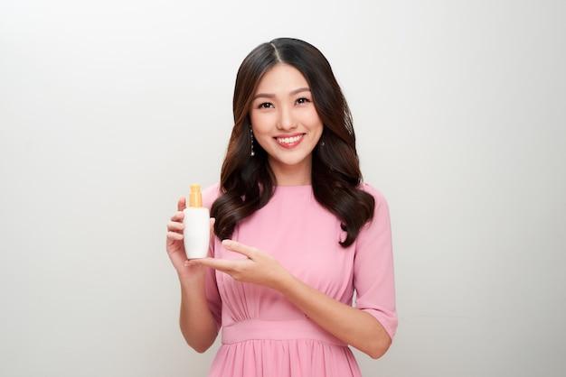스킨 케어 제품을 보여주는 웃는 젊은 아시아 여자.