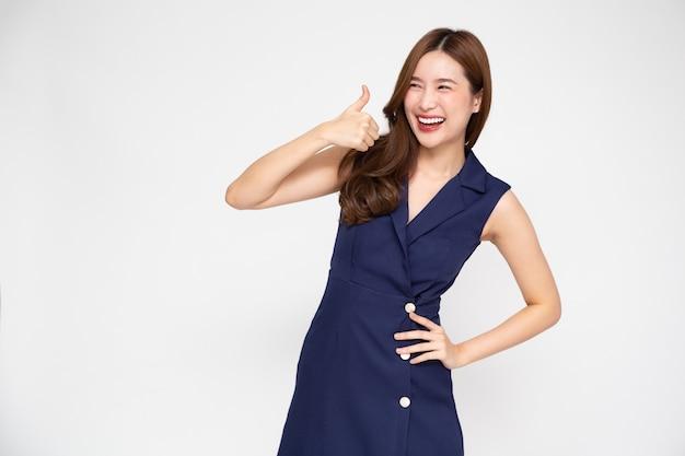 Улыбающаяся молодая азиатская женщина показывает палец вверх, изолированные на белом фоне