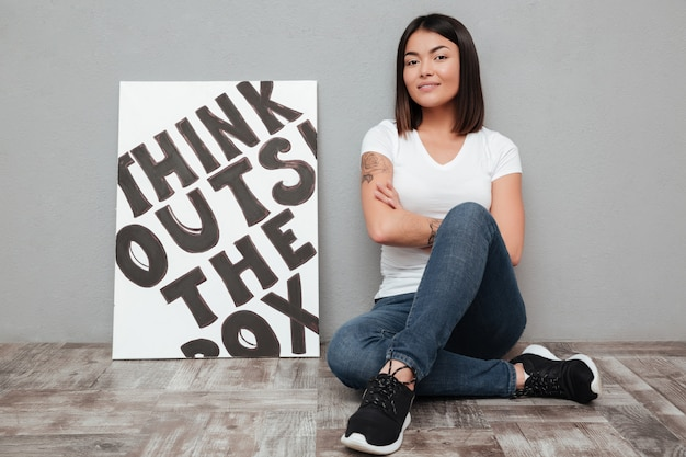 Smiling young asian woman sitting isolated