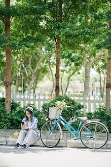自転車の隣の道路に座って、カクテルを飲み、友人にテキストメッセージを送る若いアジアの女性の笑顔