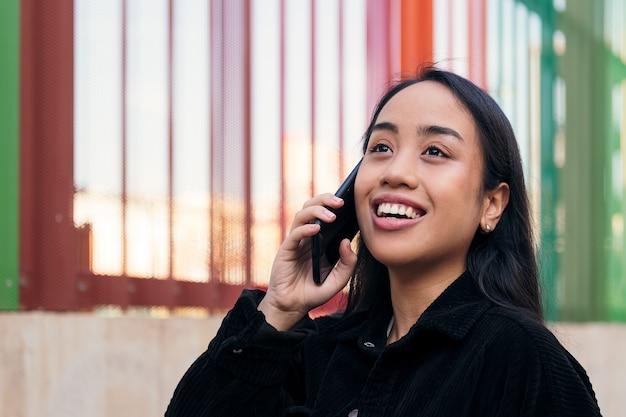 야외에서 전화 통화를 하는 웃고 있는 젊은 아시아 여성
