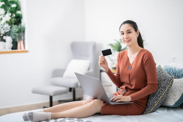 집에서 신용카드를 사용하여 웃고 있는 젊은 아시아 여성