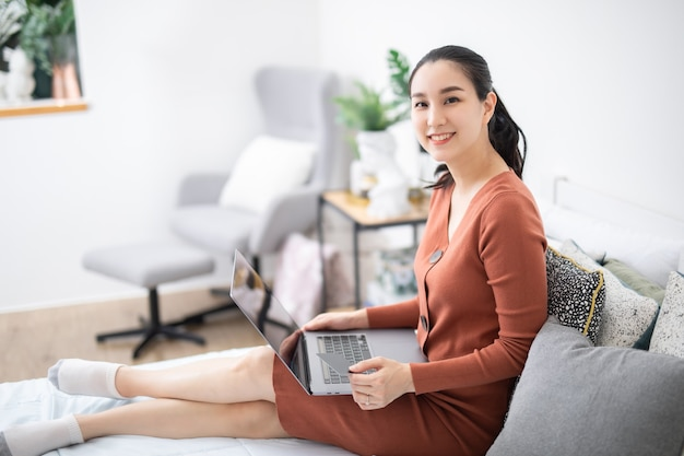 그녀의 가게에서 노트북을 사용하여 웃고 있는 젊은 아시아 여성
