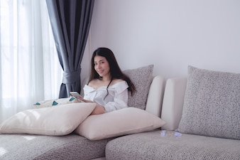 Smiling young asian woman using cell phone in living room.