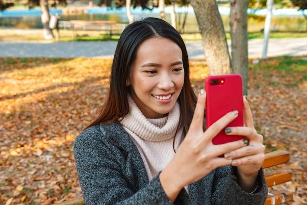 公園のベンチに座って、自分撮りをしながら、コートを着て笑顔の若いアジアの女性