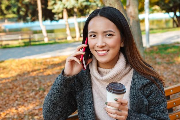 Улыбающаяся молодая азиатская женщина в пальто сидит на скамейке в парке, используя мобильный телефон