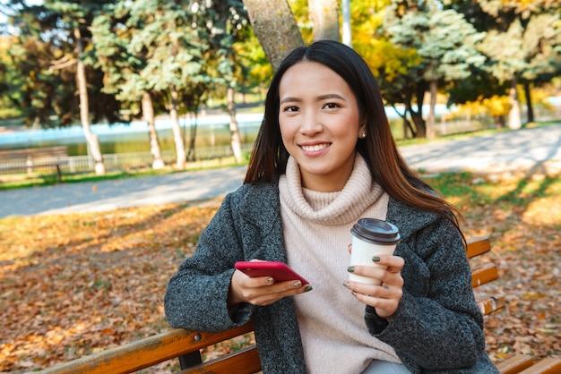 携帯電話を使用して、公園のベンチに座っているコートを着て笑顔の若いアジア人女性