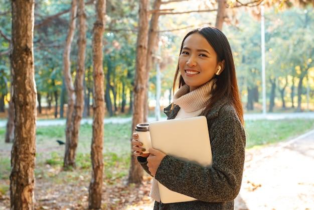 公園で屋外を歩いて、イヤホンで音楽を聴いて、持ち帰り用のコーヒーカップを持って、ラップトップを運ぶコートを着て笑顔の若いアジア人女性
