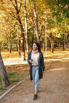 公園で屋外を歩いて、イヤホンで音楽を聴いて、持ち帰り用のコーヒーカップを持ってコートを着て笑顔の若いアジアの女性