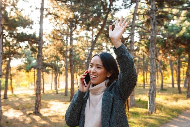Улыбающаяся молодая азиатская женщина в пальто гуляет на открытом воздухе в парке, разговаривает по мобильному телефону