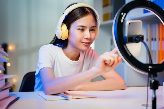 웃고 있는 젊은 아시아 여성은 헤드셋을 착용하고 인터넷에서 생방송을 하고 스마트폰으로 소셜 미디어에서 사람들과 댓글을 읽고 있습니다.