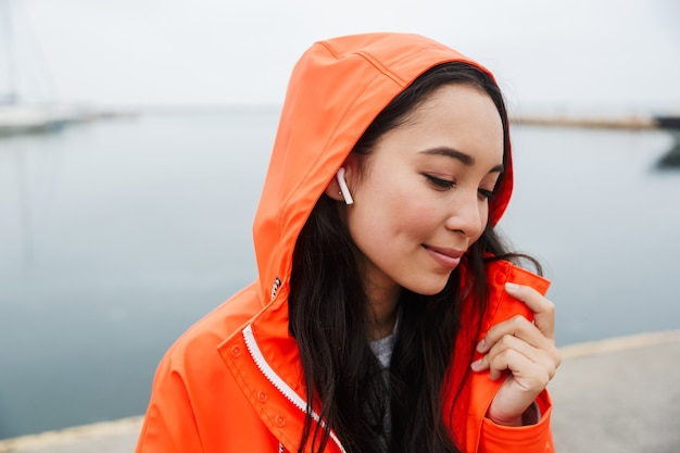 Smiling young asian woman wearing raincoat spending time outdoors walking at the coastland, listening to music with wireless earphones
