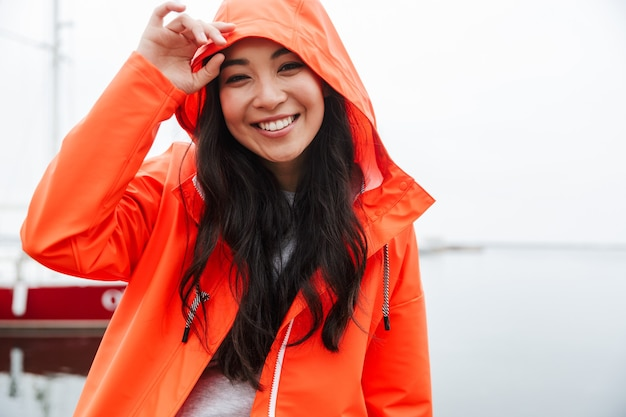 Smiling young asian woman wearing raincoat spending time outdoors walking at the coastland, looking at camera