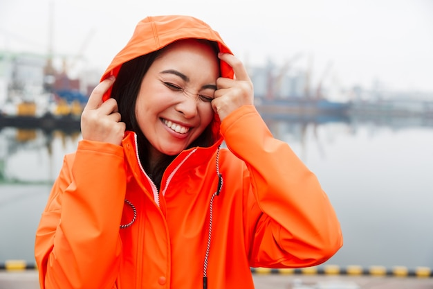 Smiling young asian woman wearing raincoat spending time outdoors walking at the coastland, posing in a hood