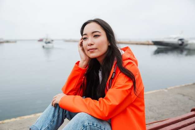 Smiling young asian woman wearing raincoat spending time outdoors walking at the coastland, sitting on a bench, looking away