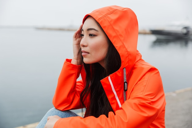 Smiling young asian woman wearing raincoat spending time outdoors walking at the coastland