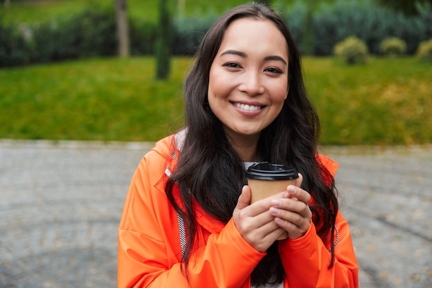 Smiling young asian woman wearing raincoat walking outdoors in the rain, holding cup of coffee