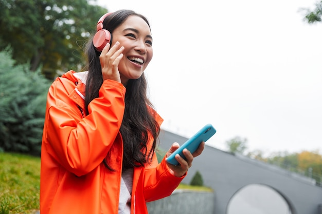 Smiling young asian woman wearing raincoat walking outdoors in the rain, listening to music with wireless headphones, holding mobile phone