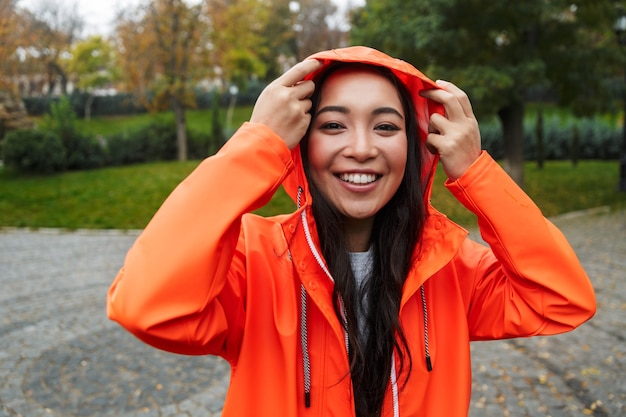 Smiling young asian woman wearing raincoat walking outdoors in the rain, posing in a hood