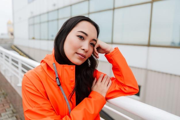Smiling young asian woman wearing raincoat walking outdoors in the rain
