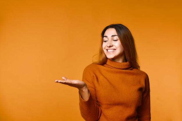 Улыбающаяся молодая привлекательная кавказская девушка одета в пуловер