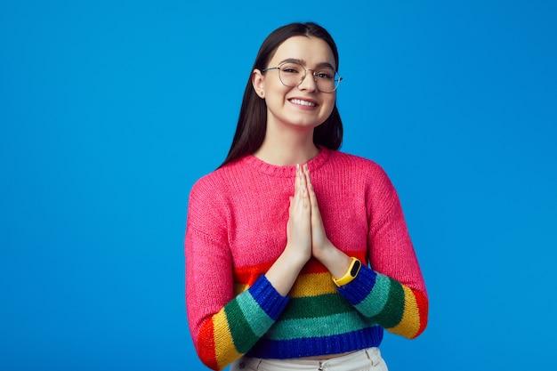 Улыбающаяся молодая привлекательная девушка показывает молящийся жест в радужном свитере