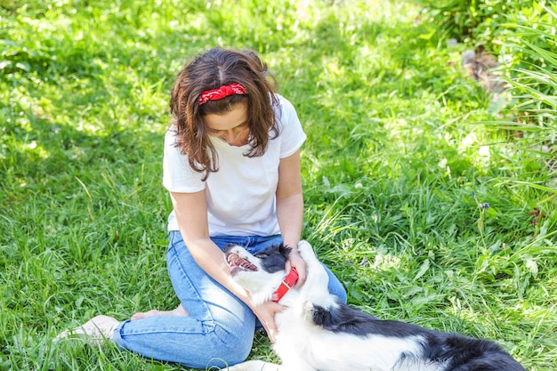 Smiling young attractive woman playing with cute puppy dog border collie in garden or city park