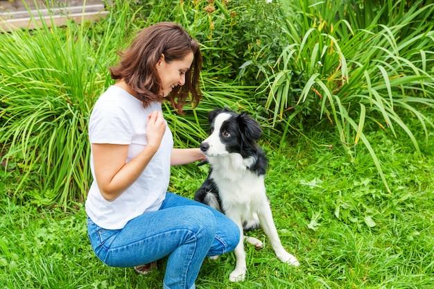 여름 정원 또는 도시 공원 야외 배경에서 귀여운 강아지 강아지 보더 콜 리와 함께 연주 젊은 매력적인 여자를 웃 고. 개 친구와 여자 훈련 트릭입니다. 애완 동물 관리 및 동물 개념.