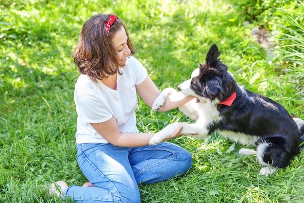 夏の庭や都市公園の屋外の背景でかわいい子犬の犬のボーダーコリーと遊ぶ若い魅力的な女性の笑顔。犬の友達との女の子のトレーニングトリック。ペットの世話と動物の概念。