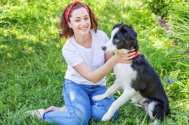 Улыбается молодая привлекательная женщина, играя с милый щенок бордер-колли в летнем саду или городском парке на открытом воздухе.